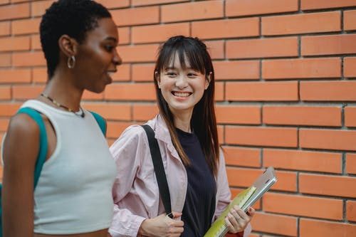 Happy multiethnic students chatting and outside brick building