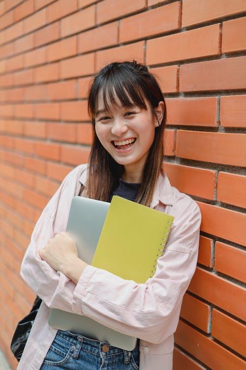 Joyful Asian female student leaning on university brick wall