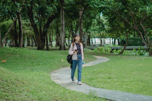 Full body of positive young Asian female in casual outfit listening to music via earphones and smartphone while walking on pathway in park