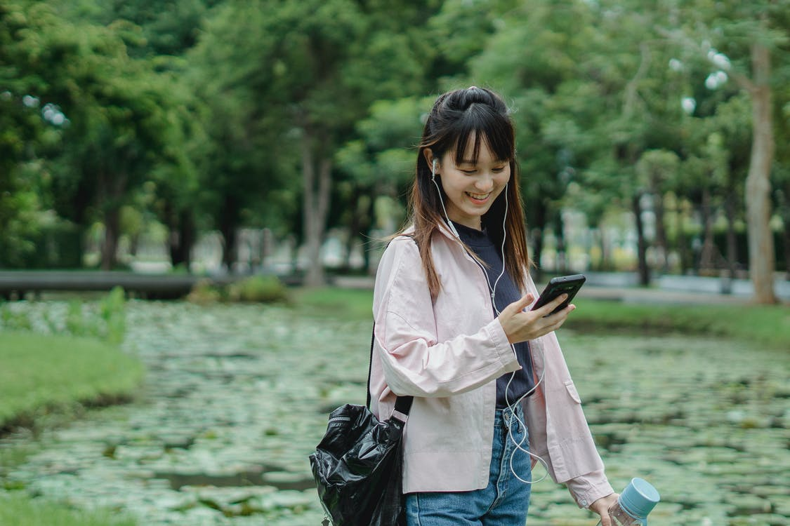 Positive ethnic woman with smartphone and earphones