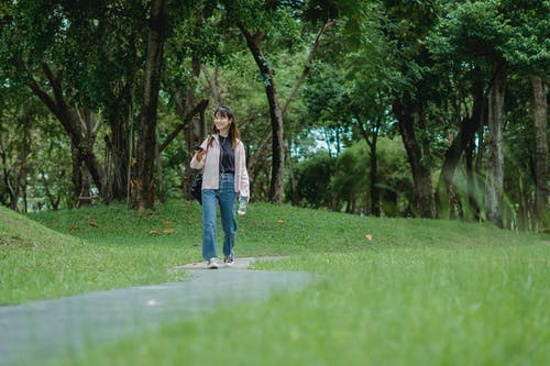 Full length of cheerful young Asian female in casual outfit strolling along green park and talking on phone using earphones