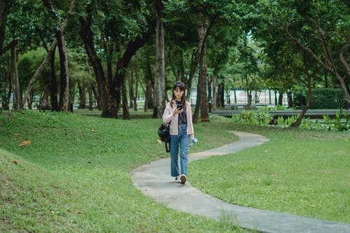 Concentrated woman text messaging while strolling in park