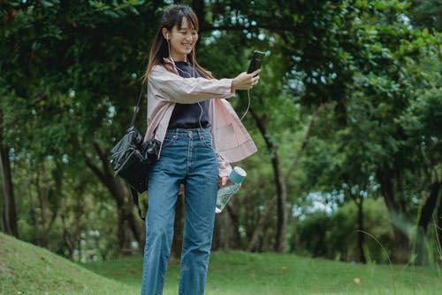 Cheerful young Asian female in casual outfit video calling using earbuds while walking in green park