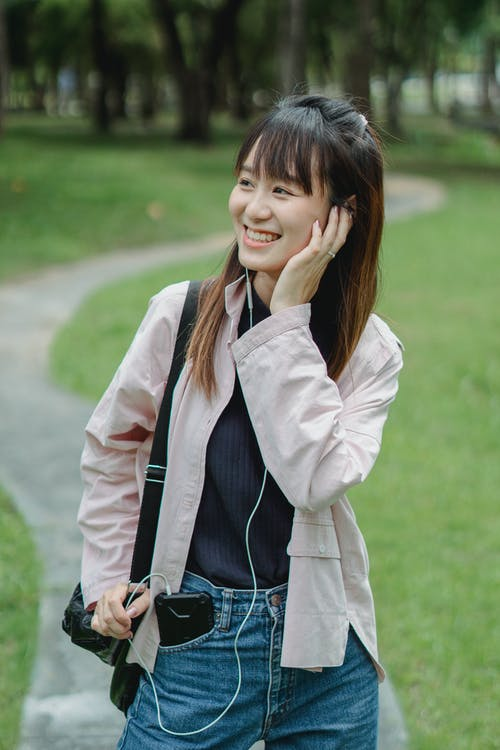 Cheerful young Asian female in casual clothes standing on pathway in park while walking and listening to music via earbuds