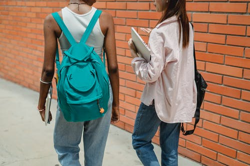 Crop multiethnic students with backpacks