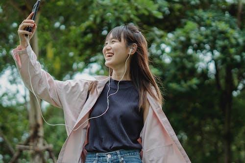 Happy woman with smartphone and earphones