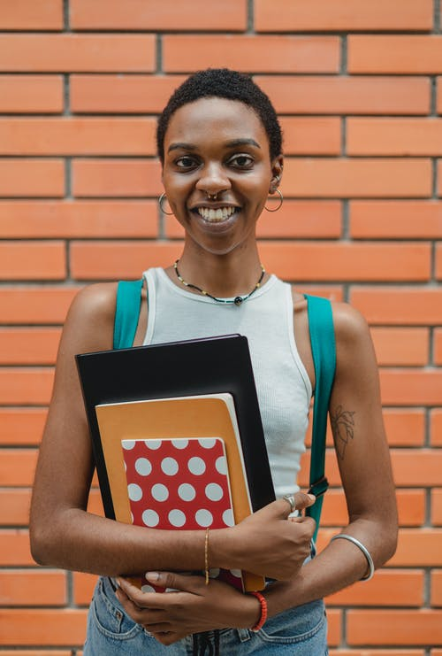 Cheerful young black female with short hair in casual outfit standing against brick wall with folder and copybooks looking at camera