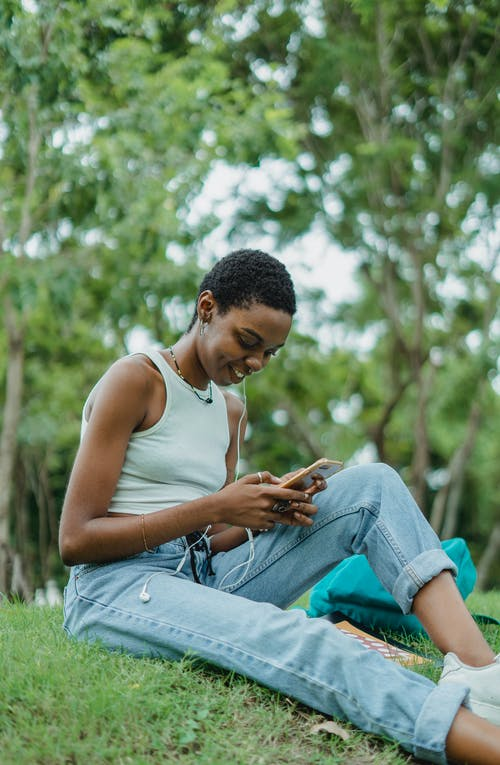 Young African American female in casual outfit sitting on green grass in park and text messaging via smartphone