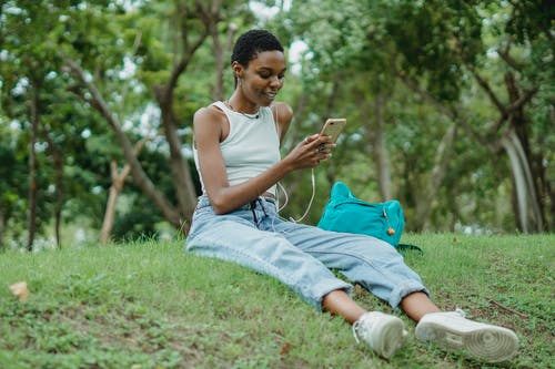 Full length of young African American female in casual wear listening to music via smartphone with earphones while resting on grass in park