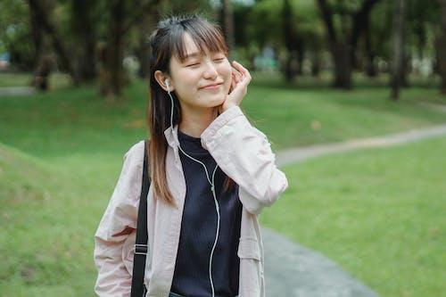 Asian woman enjoying music via earbuds