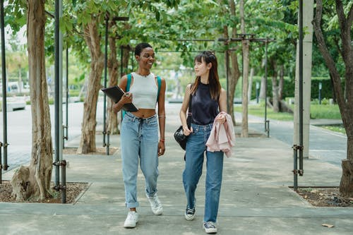 Young multiethnic female friends strolling along walkway between trees and talking to each other