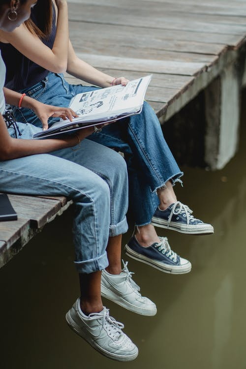 Friends reading book on bridge