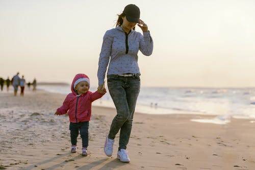 Little girl walking with mother on beach