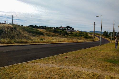 Immagine gratuita di asfalto, cielo nuvoloso, erba, persona