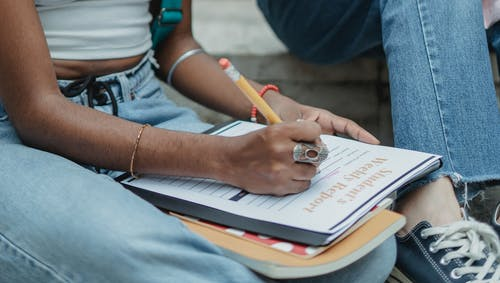 Crop black student writing report