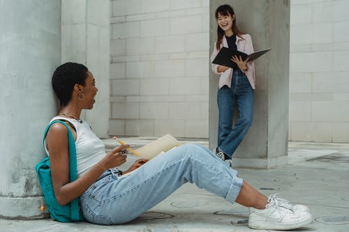 Cheerful young multiracial female students in casual clothes laughing while taking notes and reading papers making project together