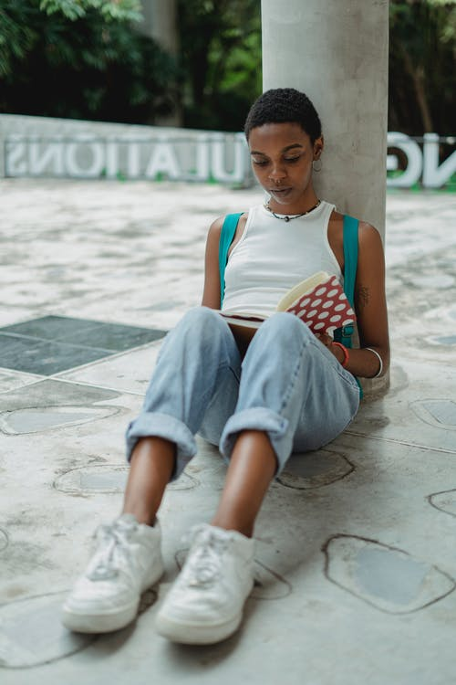 Focused young African American female student in casual clothes sitting on ground and reading notes in notebook