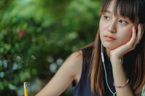 Thoughtful ethnic woman with earphones
