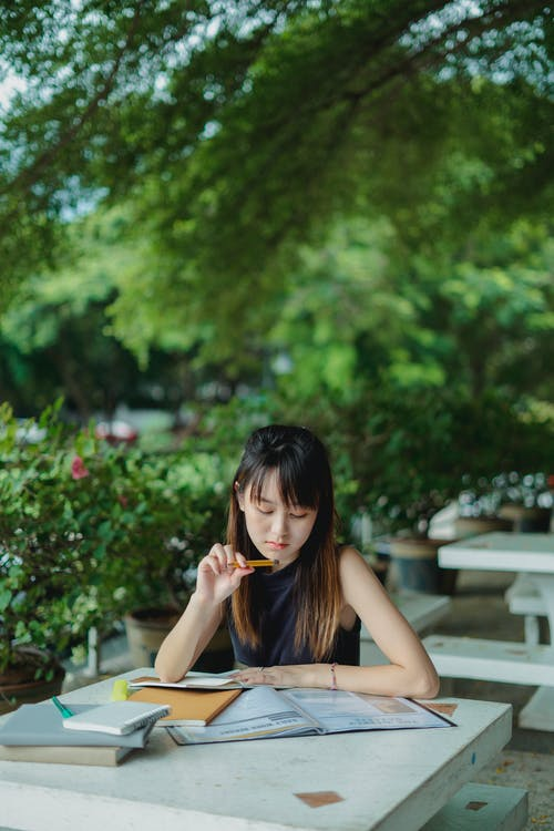 Young Asian lady studying with books outdoors in casual outfit in summer day at table