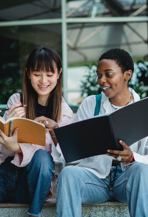 Happy young multiracial women in casual clothes preparing for exam with notebook outside in summer day