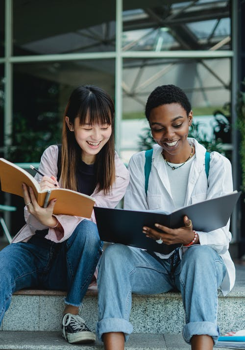Smiling young multiracial ladies sitting outside in casual outfit with notebooks and talking with each other in daytime