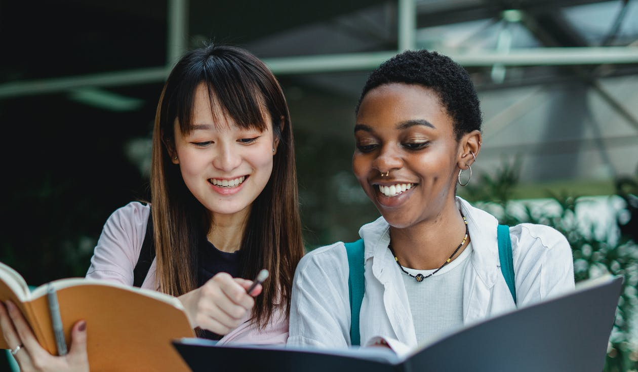 Multiracial female students studying and talking outside