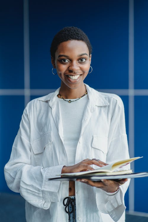 Smiling African American female student in casual clothes standing with notebooks on blue background and looking at camera