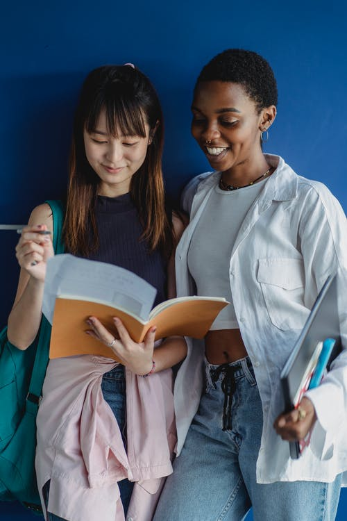 Multiethnic classmates standing with notebooks near wall