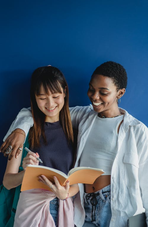 Smiling young multiracial female students standing on blue background in casual outfit with notepad and pen while talking