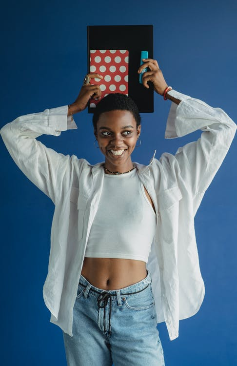 Smiling African American female student standing alone with marker and notepad in casual outfit on blue background and looking away