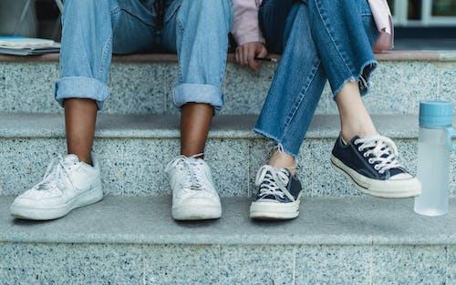 Безликие многонациональные подружки сидят на ступеньках на улице