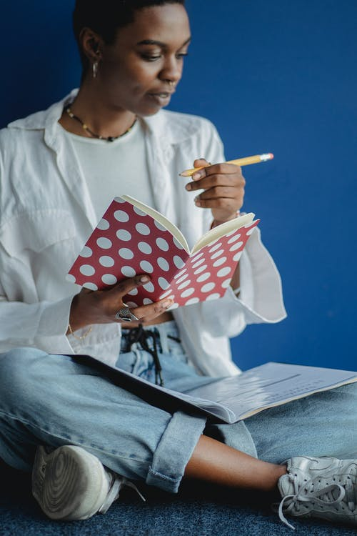 Crop African American female learner taking notes in notepad while reading document for homework