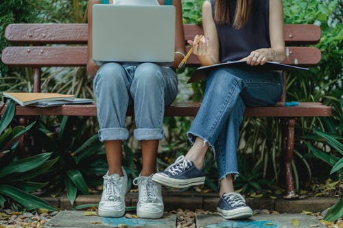 Diverse students using laptop for teamwork on bench