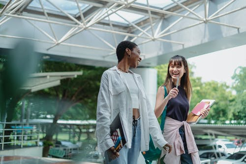 Cheerful multiracial female students having conversation while carrying notebooks under glass roof and looking at each other