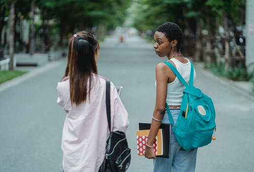 Back view of diverse female students carrying backpacks and supplies for university while talking in park