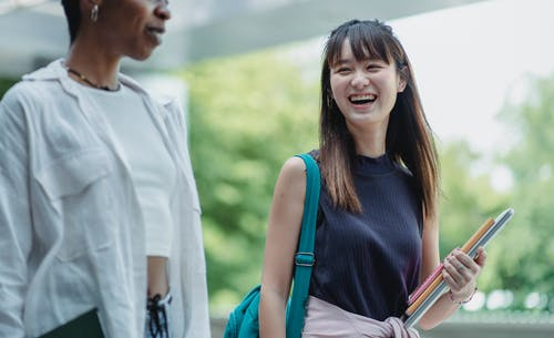 Positive Asian student laughing while walking with ethnic friend