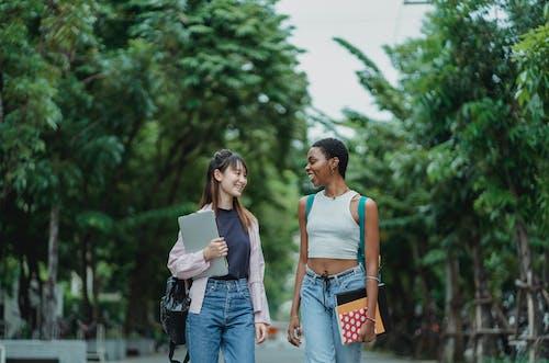 Smiling multiethnic girlfriends walking along green alley