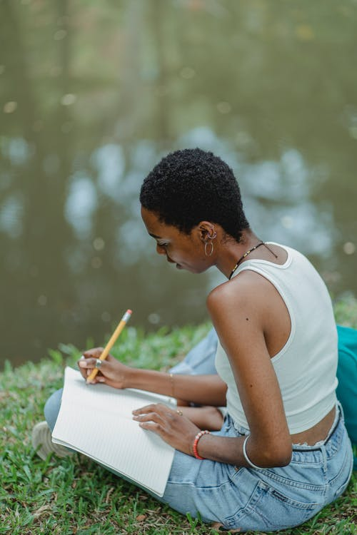 Serious black student writing essay in notebook in park