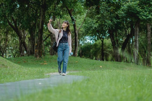 Smiling young Asian woman talking via smartphone while walking in park