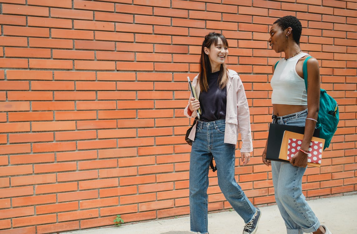 Positive African American female student with notebooks and backpack communicating with female friend wearing jeans while walking together near brick wall of university