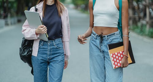 Crop multiracial schoolgirls carrying laptop and notebooks walking along park