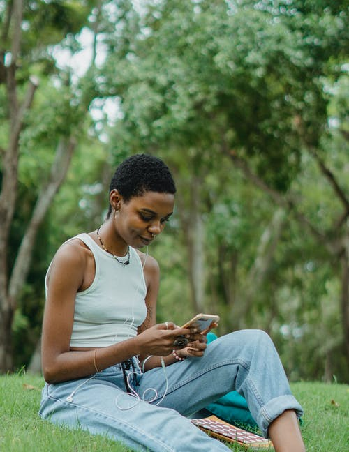 Young cheerful African American woman wearing white top and jeans sitting on grass in park and making video call on contemporary smartphone