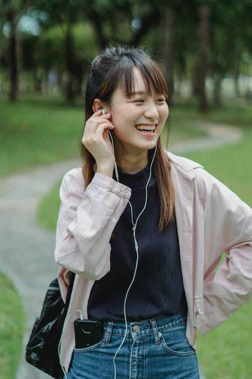 Parkta Kulaklık Ile Akıllı Telefon Aracılığıyla Konuşan Mutlu Asyalı Genç Bayan