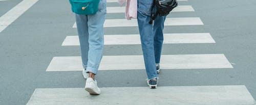 Unrecognizable women wearing jeans crossing city street