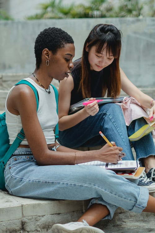 Concentrated black female student explaining project details to smiling Asian female friend while spending time together in urban street