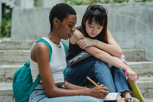 Black female student taking notes while sitting together with Asian friend on concrete stairs and preparing university project