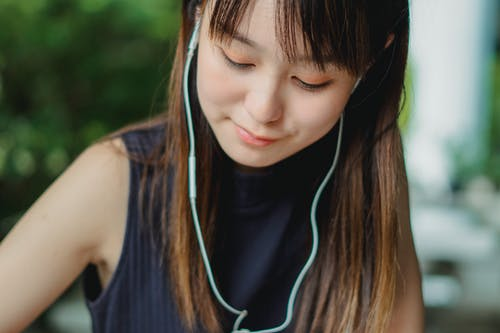 Crop calm young Asian female in blue tank top listening to music with light blue earphones and looking down