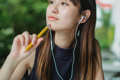 Dreamy young Asian lady listening to music in earphones