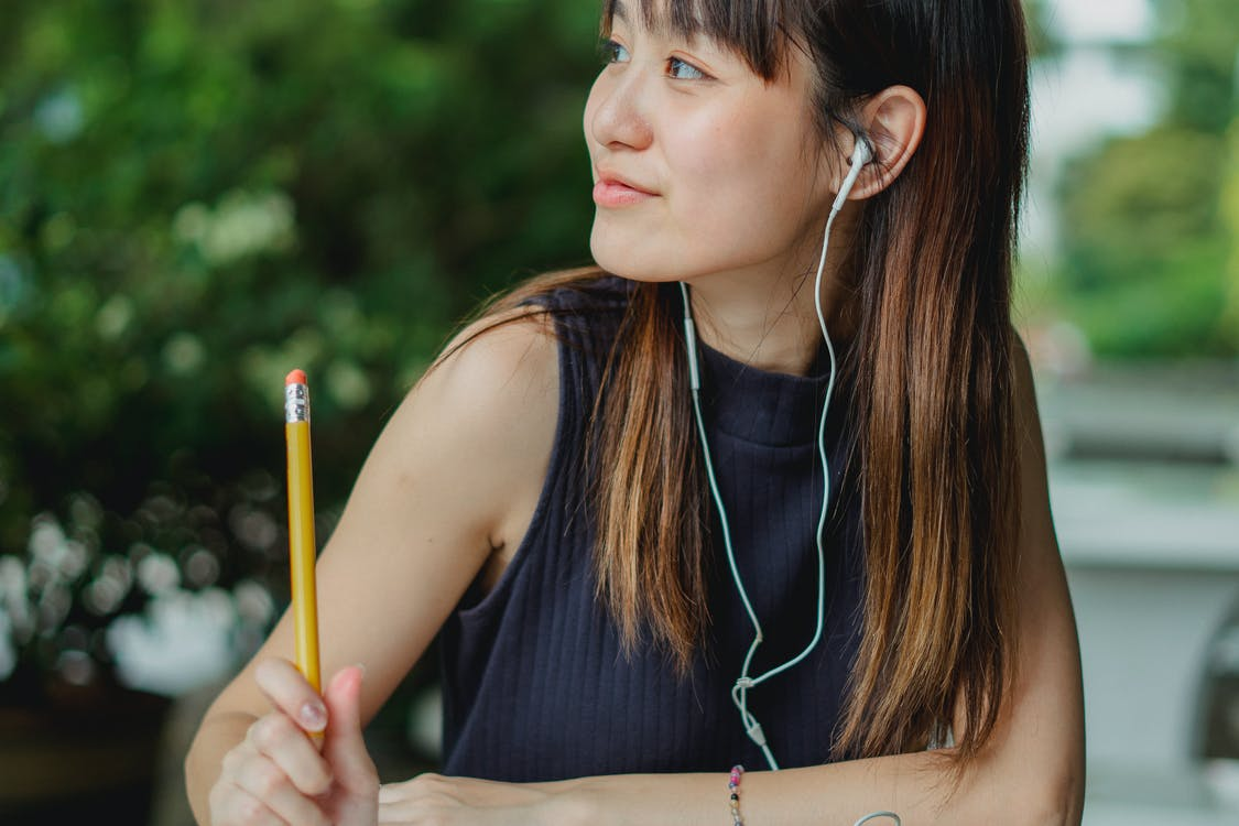 Happy young Asian student listening to music while studying at table in park