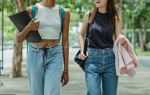 Two Young Women Walkng In The Street